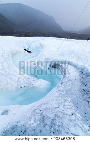 Milky blue meltwater running from Longyear glacier in Svalbard. Strong snowfall and cloudy sky