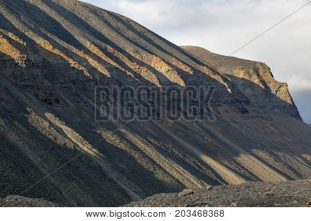 Beautifully carved rocky mountain in glacier moraine in evening sunlight with harsh shadows above Longyearbyen town in Svalbard Norway
