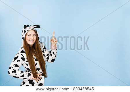 Happy teenage girl in funny nightclothes pajamas cartoon style pointing up with positive smiling face expression studio shot on blue. Advertisement concept