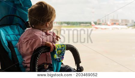 Baby girl in the stroller looks out the window at the planes at the airport