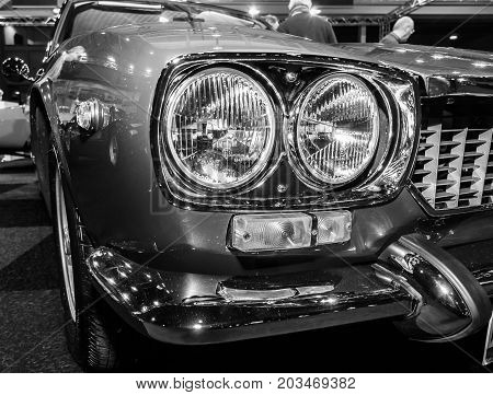 MAASTRICHT NETHERLANDS - JANUARY 09 2015: Headlamp of a sports car Maserati Mexico 4.2 (Tipo AM112) 1972. Black and white. International Exhibition InterClassics & Topmobiel 2015