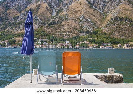 Two chairs on the beach. Montenegro. pier. View of the opposite shore.