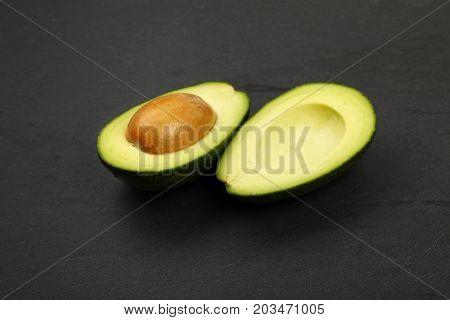 Two Halves Of Avocado On Black Slate Board