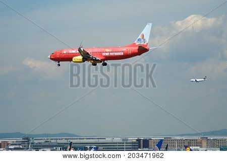 FRANKFURT, GERMANY - JUL 09th, 2017: TUIfly AIRLINES Boeing 737-800 with red advertisement lands at Frankfurt airport, Boeing 737 Next Gen, MSN 30883, Registration D-AHFZ, TUIfly-a German leisure airline owned by the travel and tourism company TUI Group.
