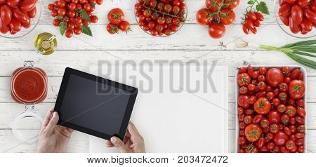 hands with digital tablet above on white cutting board with tomatoes on kitchen white wooden worktop copy space top view