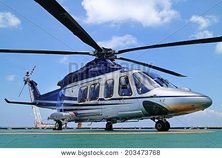 Helicopter or chopper land at oil and gas platform area for get and sent passenger from onshore hangar to offshore platform