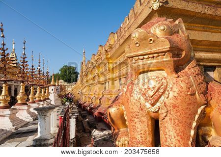 The bottom platform of the buddhist Shwezigon Pagoda in the town of Nyaung-U near Bagan in central Burma with a chinthe lion statue