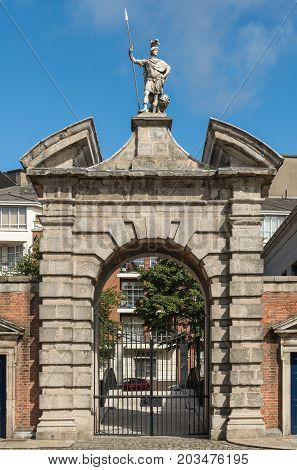 Dublin Ireland - August 7 2017: Monumental beige stone entrance gate to central square of Castle. Statue of Roman guard and lion on top. Closed with view on outside street. Blue sky.