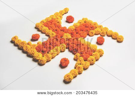stock photo of hindu auspicious symbol called Swastika made using marigold flower or zendu or genda phool, Flower rangoli in the shape of Swastika for diwali/pongal/onam over white background