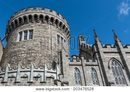 Dublin Ireland - August 7 2017: Thick central gray stone watch tower of The Castle under clear blue sky. Part of castle church on the side.