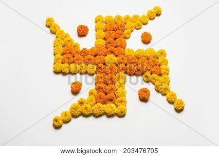 stock photo of hindu auspicious symbol called Swastika made using marigold flower or zendu or genda phool, Flower rangoli in the shape of Swastika for diwali/pongal/onam over white background
