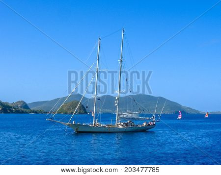 Sailboat navigates in the waters of the Archipelago of Les Saintes, Guadeloupe in the blue Caribbean sea.