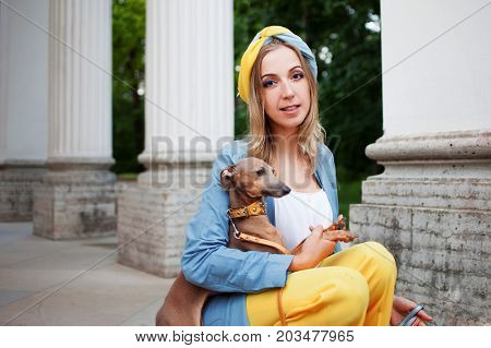 Stylish lady in yellow pants, blue jacket and a turban