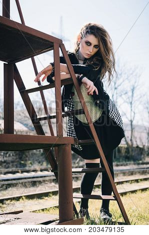 Outdoor portrait of the pretty grunge (rock) girl at the railroad