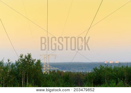 The tip end anchor metal supports of overhead power lines with wires is on the slope of the hill above the forest trees on a background of soft orange colorful sunset and the city buildings