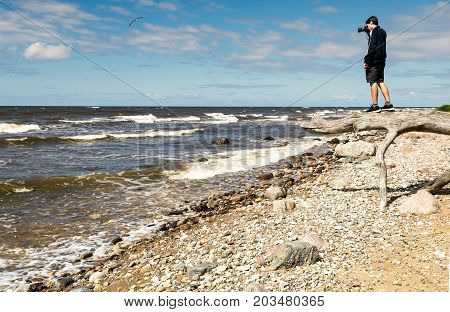 Coastal landscape with a young man looking into the distance through viewfinder of DSLR camera