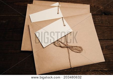 Note from a paper on a cord of an envelope from kraft paper on a wooden table