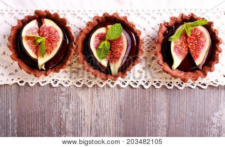 Chocolate mini tarts with chocolate ganache filling and fig on top. Overhead shot with copyspace