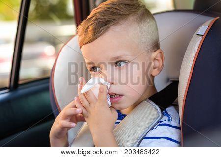 Cute little boy in a car seat with a handkerchief