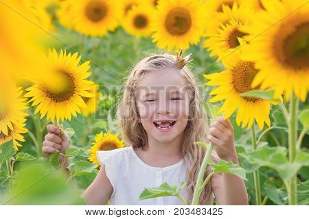 Happy little girl playing in the field of sunflowers