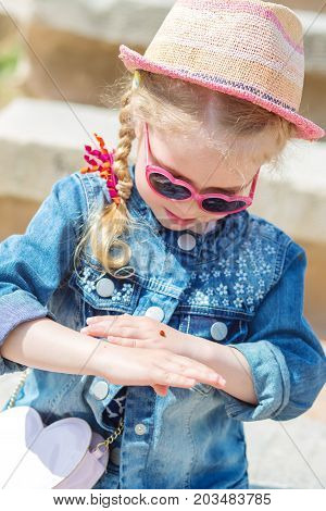 little girl is looking at ladybug on her hand.