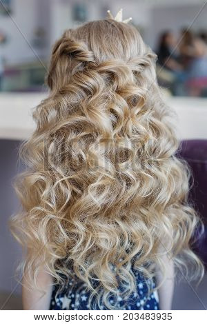 Little girl with perfect hairstyle curl hair with a crown on his head