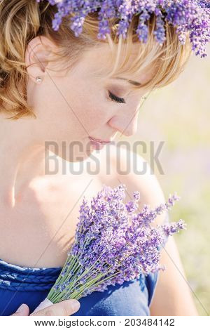 beautiful pregnant young woman in a white dress in lavender field