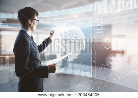 Side view of young businessman drawing abstract digital business interface in blurry office interior. Future concept. Double exposure