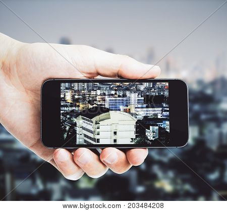 Male hand taking photograph of night city with smartphone