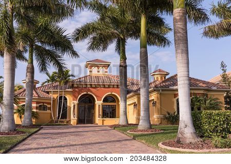 Typical Southwest Florida luxury concrete block and stucco home in the countryside with palm trees tropical plants and flowers grass lawn and pine trees. Florida. South Florida single family house