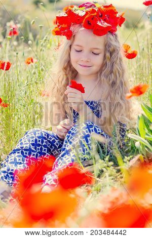 Little cute little girl in a wreath of poppies summer time