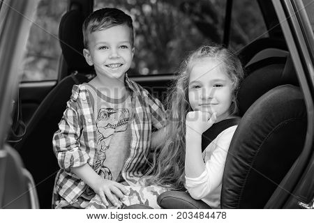 Cute girl and boy sitting in car back seat (Black and white)
