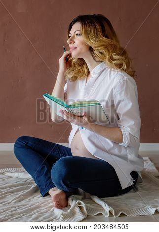 beautiful healthy pregnant woman sitting on a knitted plaid and reading