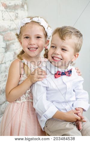 Two charming children stand having joined hands. Girl is dressed in a elegant dress. On the head of her a wreath. Boy has a bowtie. Children laugh.