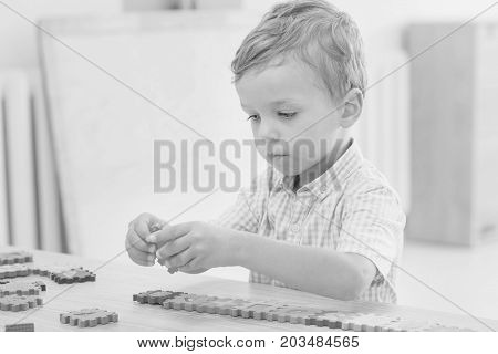 focused cute little child collects puzzles with numbers at the table ( black and white )