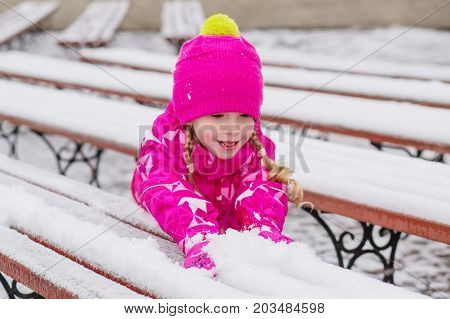 Little pretty girl playing with snow lying on benches