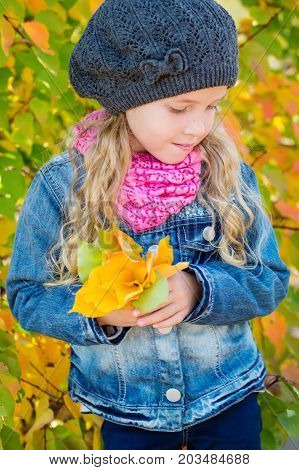 adorable little girl with autumn leaves in thepark on a walk