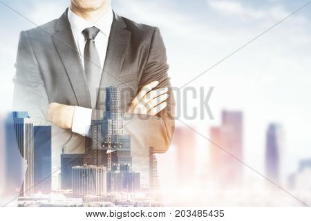 Front view of young businessman with folded arms standing on abstract city background with copy space. Tomorrow concept. Double exposure
