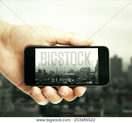 Male hand taking photograph of city with smartphone