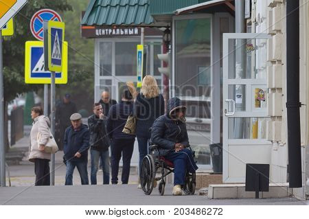 KAZAN, RUSSIA - September 9, 2017: Disabled beggar poor man with wheelchair on the Ostrovskogo street asking for money or food, telephoto