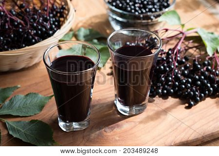 Two Glasses Of Elderberry Syrup On A Wooden Table