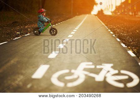 Little boy riding a balance bike on a cycling way