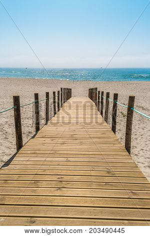 Wooden walkway over the sand dunes to the beach. Beach pathway in Praia de Paramos Espinho Portugal