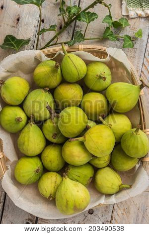 Whole figs in wicker basket on top of a rustic wooden table.