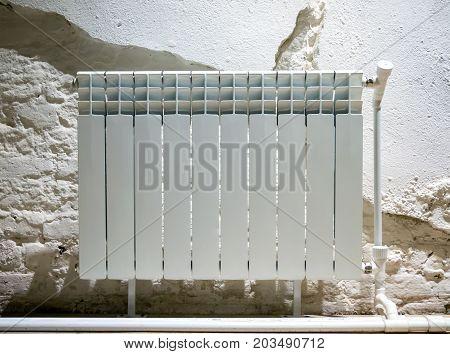 Bimetallic radiator near the wall with crumbling plaster