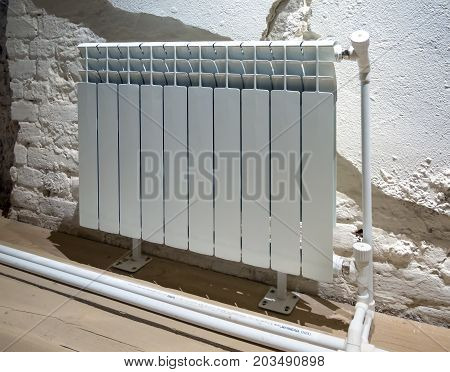 Modern radiator on the background with a partially plastered wall
