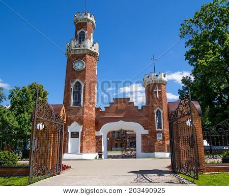 Ramon Russia - June 07 2017: The central entrance to the castle of Oldenburg with massive forged gate and a clock tower Ramon settlement of the Voronezh region