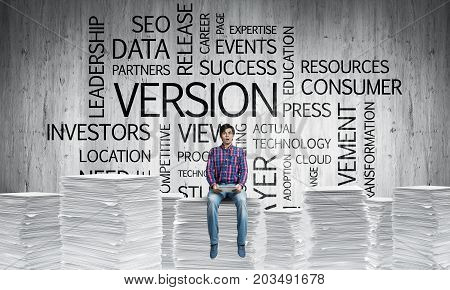 Young man in casual wear sitting on pile of documents with business-related terms on background. Mixed media.