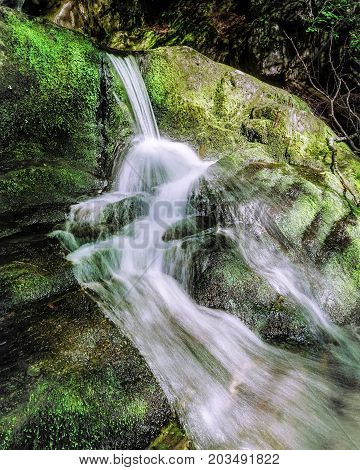 A small water fall spills along moss covered rocks. Water Fall photograph was taken in the summer when there was not much water flowing int he brook.