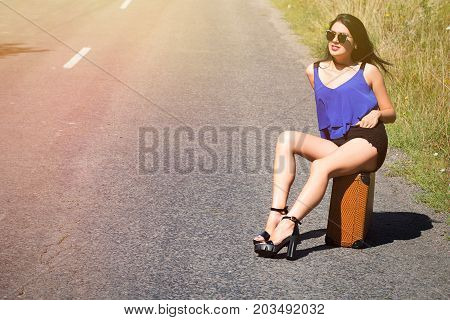 Happy Beautiful Girl Traveler With A Suitcase On The Road, Hitchhiking. The Concept Of Travel, Adven